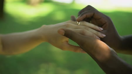 oświadczyny : Multiracial marriage, male hand puts golden ring on brides finger, wedding time