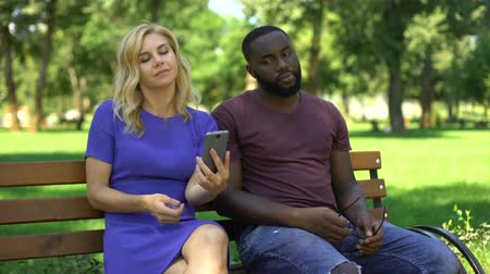neglected : Caucasian woman playing smartphone on date in park, ignoring worried boyfriend Stock Footage
