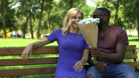glass master : Black man presents bouquet of flowers to sad blond woman sitting in park, date
