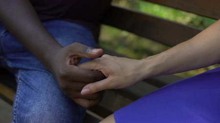together trust : Afro-american male holding female hand, multiracial love, stereotype, closeup