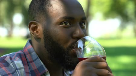 şarap : Black man smiling and drinking wine, gathering with friends in park, relax time