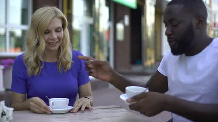 traer : People drinking coffee in outdoor cafe, romantic date of happy mixed race couple Archivo de Video