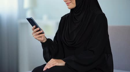 foulard : Smiling arab woman reading smartphone message, online communication, chatting