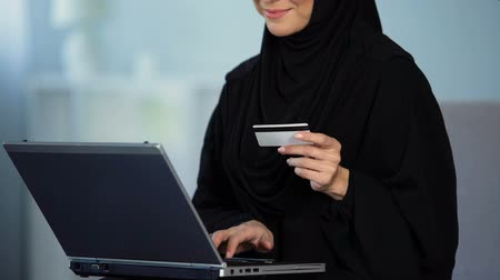 entering : Pretty female in hijab entering credit card number on laptop, shopping online