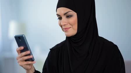 islámský : Beautiful muslim lady watching online video on smartphone, modern technology