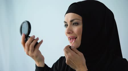melisa : Female in hijab applying lipstick holding hand mirror, femininity and beauty Stok Video