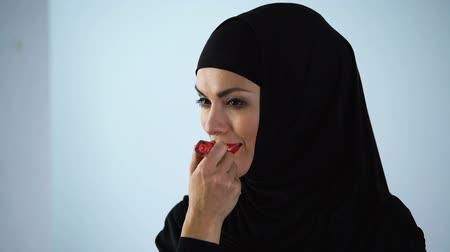melisa : Muslim female applying red lipstick, bright make-up, style and beauty appearance