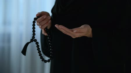 cerimonial : Arab female in hijab counting prayers by rosary in hand, religious forgiveness