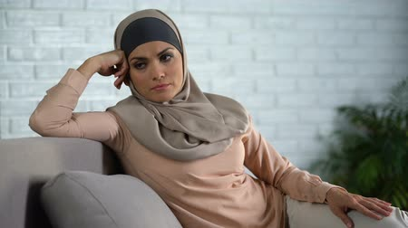 desesperado : Sad arab housewife sitting on sofa at home, relations crisis, thinking trouble