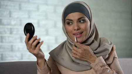 melisa : Pretty arab housewife applying lip gloss, looking in small mirror, beauty, style Stok Video