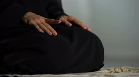 ajoelhado : Woman in traditional black hijab kneeling on prayer mat mosque, islamic culture Vídeos