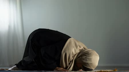 duch Święty : Kneeling arab woman prostrating on islamic praying rug, religious worship, faith Wideo
