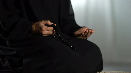 ajoelhado : Praying woman with traditional islamic beads in hand kneeling on rug in mosque