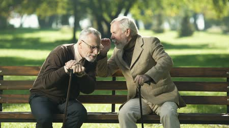 listens : Senior gentlemen talking to his hearing impairment old friend, health problems Stock Footage