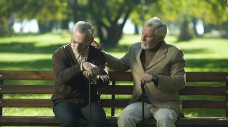 embarrassed : Old man supporting depressed friend, sitting in park near nursing home, lost