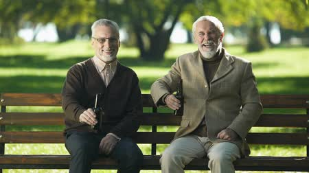 семидесятые годы : Two smiling senior friends showing beer bottle into camera, relaxing in park