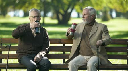 t şeklinde : Old men enjoying hot tea from thermo cups, siting on bench outdoor, retirement