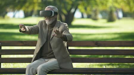 восхищенный : Amazed senior men using VR headset outdoors, modern technologies experience Стоковые видеозаписи