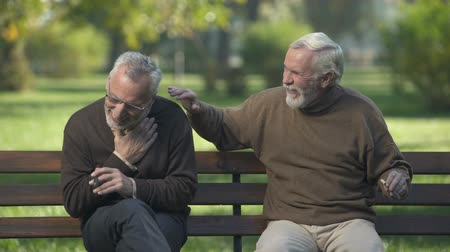 cigar : Elderly male coughing while smoking cigar, friends enjoying park rest together