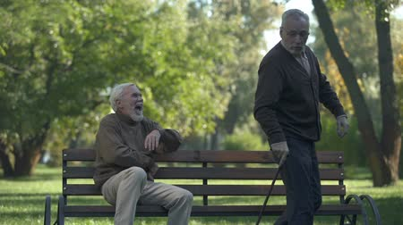 comics : Aged man joking with friend kicking butt, friendship humor, having fun, leisure Stock Footage