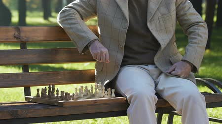 estratégico : Thoughtful grandfather moving chess figures on board, playing alone in park