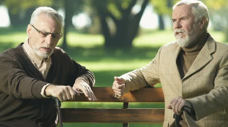 remember : Retired gentlemen talking in park, trying to remember, aging memory impairment Stock Footage