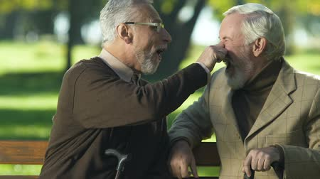 travessura : Humorous aged man joking with friend in park, pinching nose, old age positivity Vídeos