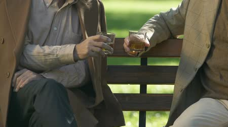 элита : Senior friends clinking and drinking whisky, sitting park, countryside weekend