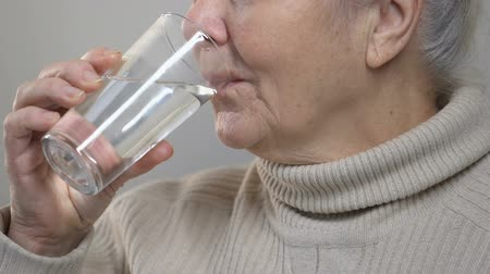 nyel : Wrinkled elderly woman drinking water, feeling thirsty, taking medicine, closeup Stock mozgókép