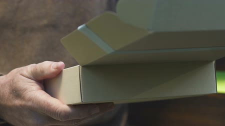 memories photos : Old man opening cardboard box with letter, received parcel from children Stock Footage