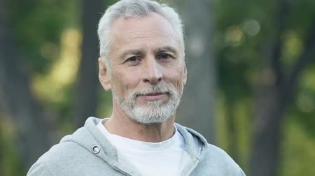 good looking guy : Handsome mature man smiling into camera, sports activity, healthy lifestyle Stock Footage