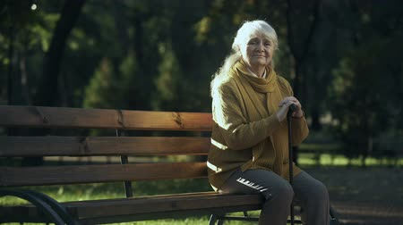 álmodozás : Sad lonely old woman sitting on bench in park, abandoned elderly people alone