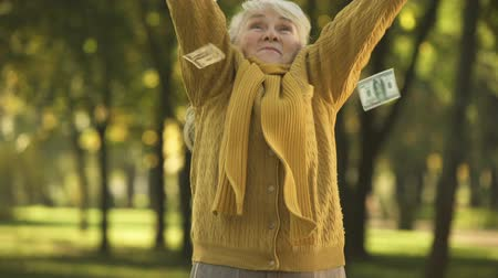 alku : Happy senior old lady throwing stack of dollar bills in park, planned retirement