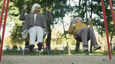 aposentar : Two senior ladies enjoying ride on swings in park, elderly friends, retirement