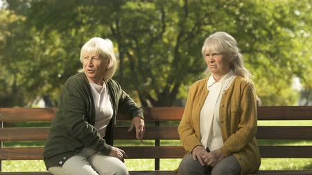 passerby : Two grumpy old ladies judging passerby people, sitting on bench in park, pension