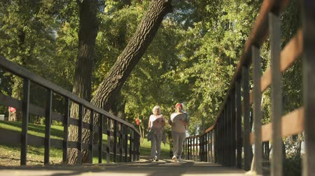 em forma de : Two woman friends jogging together in park in morning, active healthy lifestyle