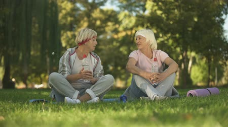 érettség : Middle age woman and her mother talking after doing exercises and yoga in park