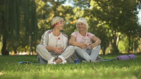 maturità : Two women showing thumbs up sitting on grass after doing exercises, positive