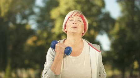arcszín : Happy middle aged woman doing morning workout with dumbbells in park, health Stock mozgókép