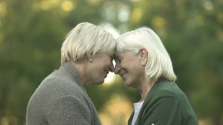 aposentar : Two mature female friends tightly hugging each other and smiling, happy meeting