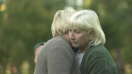 embarrassed : Depressed mature women hugging to support each other, family problems, care