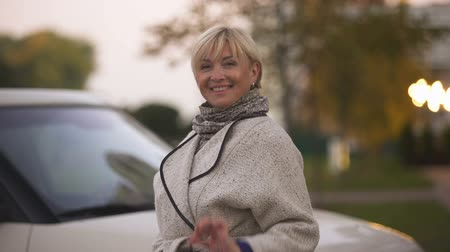 mülkiyet : Mature successful woman smiling and holding keys of new luxury car, present Stok Video