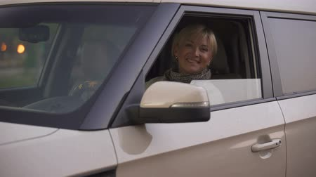 prawo jazdy : Mature blonde attractive woman smiling and looking straight from car salon