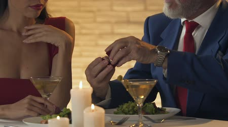 proposta : Old oligarch proposing marriage to young lady, mercantile woman grabbing ring