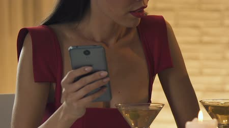 irritação : Woman using smartphone in restaurant, disappointed with boring man, closeup