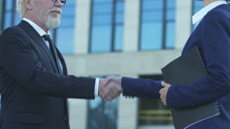 shaking hand : Old businessman shaking hands with sales manager, successful deal for startup