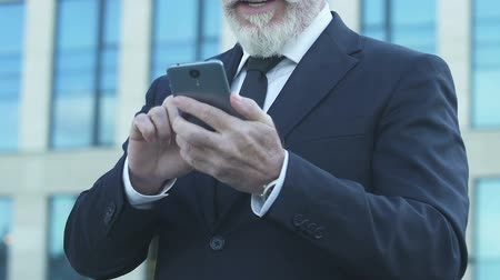 честолюбивый : Old businessman showing Yes gesture, reading good news from smartphone, closeup
