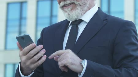 kennismaking : Old man in suit using smartphone, scrolling photos in dating app, happy emotions