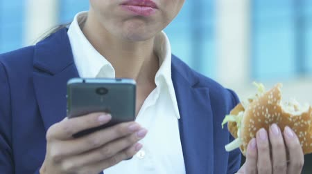 hurry up : Woman eating burger while using phone, bad nutrition due to busy lifestyle