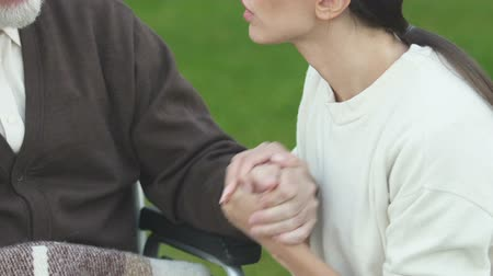 incurable : Desperate daughter saying goodbye to terminally ill father in wheelchair closeup Stock Footage